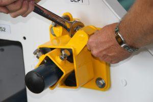 Man demonstrating how belt scraper blade mounts work